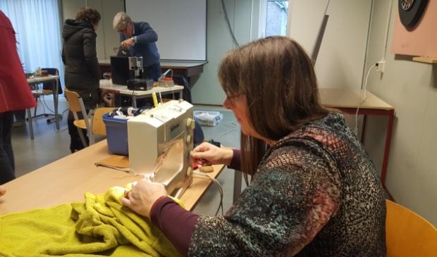 Vrijwilligster aan de slag achter de naaimachine.