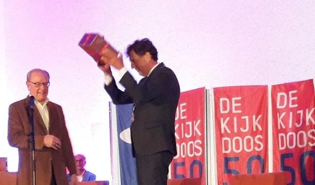 <p>De burgemeester krijgt het Kijkdoos jubileumboek van Jan van den Hazel en houdt het juichend omhoog</p>