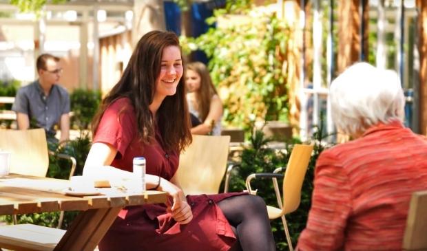 Jong en oud met elkaar in gesprek tijdens een generatiegesprek in de tuin van verbinding bij de EH