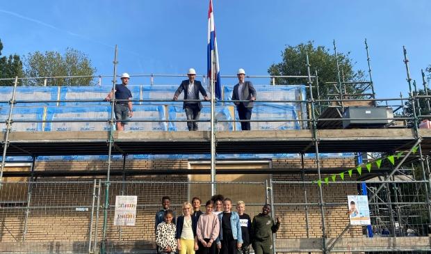 <p>wethouder Frank Berkhout en schooldirecteur Ronald Bouwman hesen de vlag onder toeziend oog van leerlingen van De Bloeiwijzer</p>