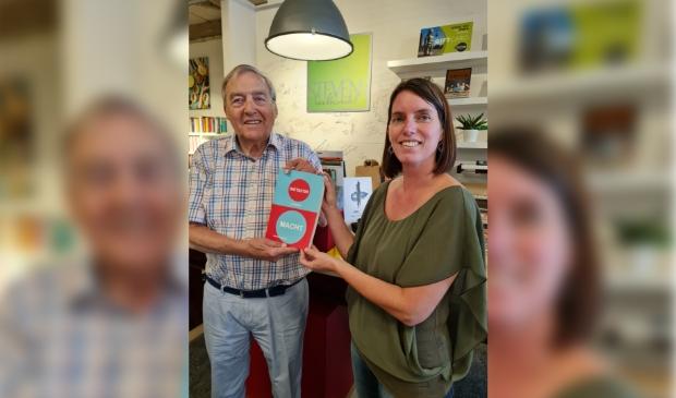 <p>Lisa Snijder, eigenares van Boekhandel Stevens krijgt het eerste exemplaar van Gerard Couvreur.</p>