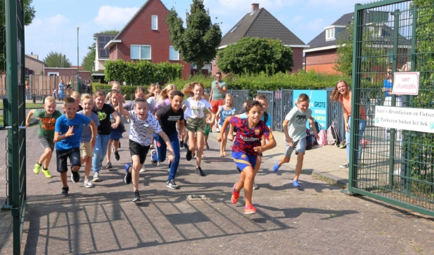 <p>De kinderen rennen het sportveld op.&nbsp;&nbsp;</p>