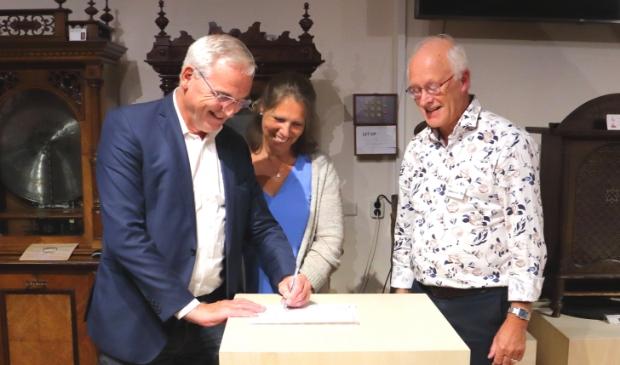 De heer Hulsbergen tekent het  schenkingsformulier van de vleugelpianola onder toezined oog van zijn echtgenote en de directeur van Het Kijk en Luistermuseum.
