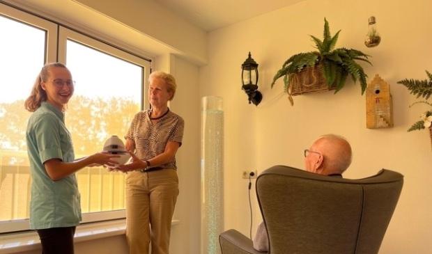 <p>Rita van Ferneij overhandigt de snoezelprojector aan een medewerker van verpleeghuis Overslydrecht.</p>