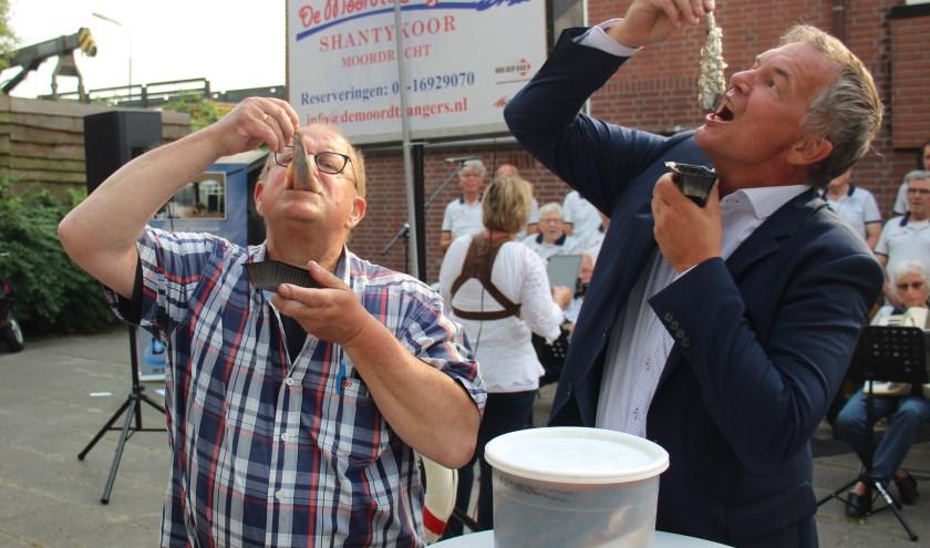 Willem Bezemer en wethouder Daan de Haas happen een harinkje, mét uitjes. (foto en tekst: Erik van Leeuwen)
