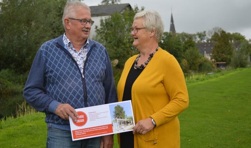 Hans en Elly van Dam in het Ringvaartpark, waar de dorskast werd bewonderd. Op de achtergrond de voormalige werkplek van Hans.