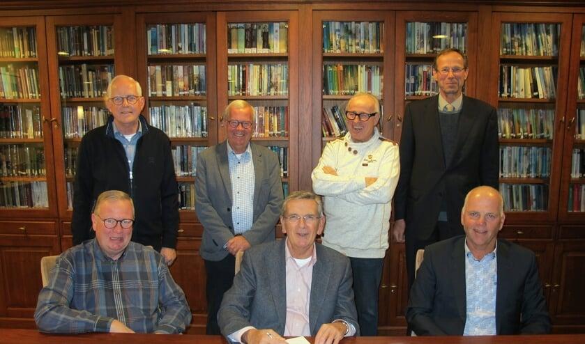 Elim-voorzitter Rinus Bosman (midden) en bouwer Leo van der Knaap zetten donderdag hun handtekeningen.