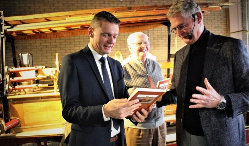 Burgemeester Nieuwenhuis krijgt uit handen van auteur Hans Zuidijk één van de twee eerste exemplaren. Toon van Nielen kijk toe.