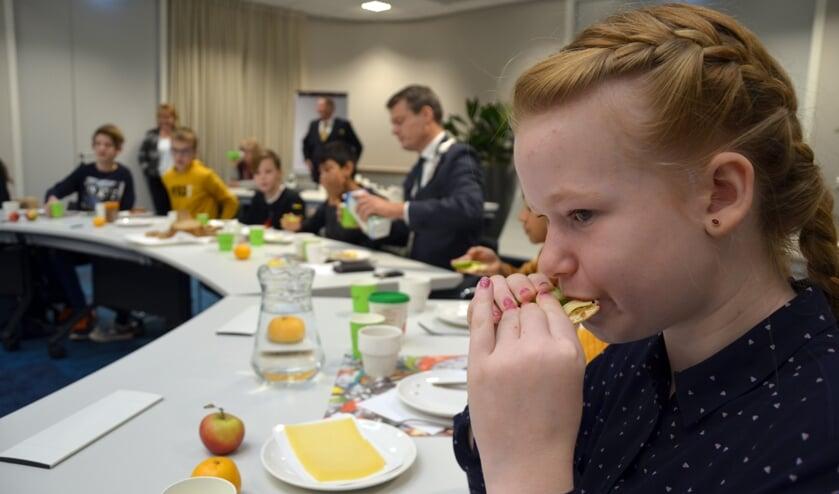 De 11-jarige Jaymee Joore geniet van een cracker met kaas in het gemeentehuis. (foto en tekst: Nicole Lamers)