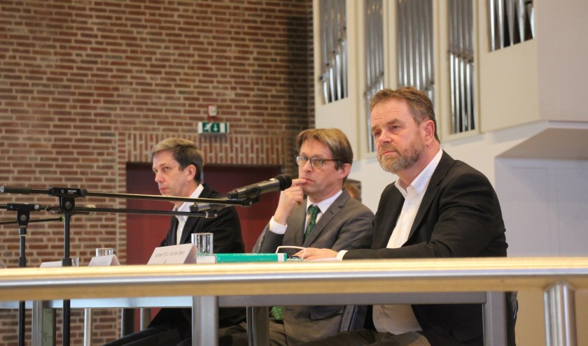 Leden van de bezwarencommissie luisteren in de Ontmoetingskerk naar de bezwaarmakers.