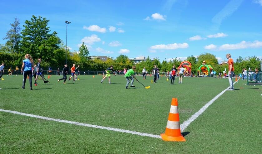 Leerlingen van De Wingerd, de Gideonschool en de PWA-school spelen in gemengde teams een potje hockey.