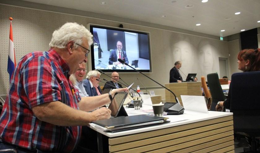 Raadslid Johan Helmer stoeit met zijn kaartje, terwijl burgemeester Servaas Stoop in vijfvoud lol heeft. (foto en tekst: Erik van Leeuwen)