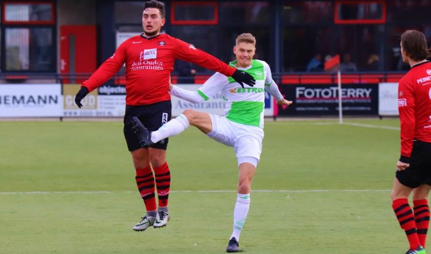Nieuwerkerker Kevin Kamerbeek wint een duel van een speler van Spijkenisse.