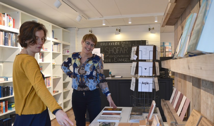 Mariëlla Koppenaal en Elly van Hoffen in de winkel met boeken, cadeautjes, kaarten en een koffiehoekje.