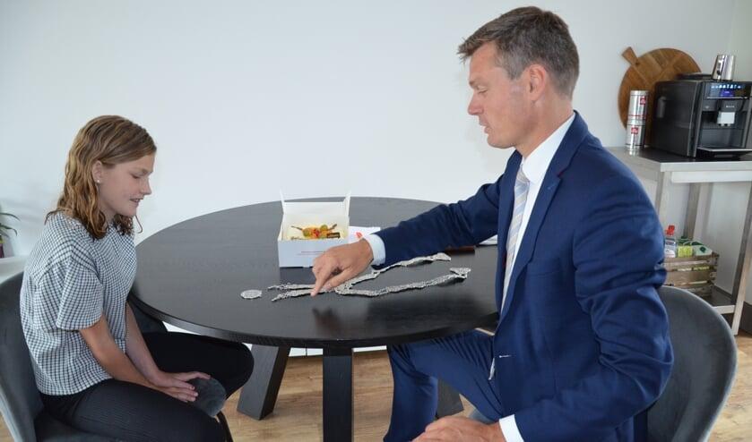 Burgemeester Evert Jan Nieuwenhuis vertelt de eerste kinderburgemeester over zijn ambtsketen.