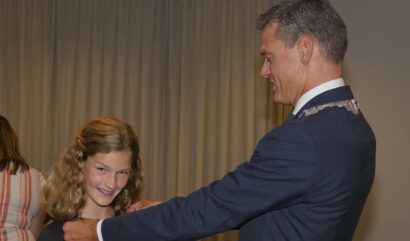 <p>Trots kijkt de eerste kinderburgemeester van Waddinxveen in de camera toen zij haar ambtsketen kreeg omgehangen door burgemeester Nieuwenhuis.</p>