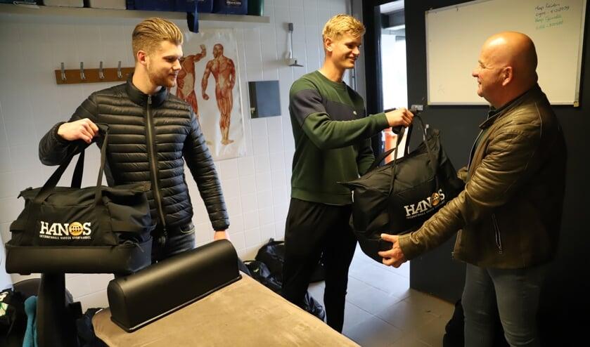 <p>Steven van Puffelen en Lennart Cok, linksback van Be Fair 1, brengen hun spullen bij materiaalman Andre van den Dop.</p>