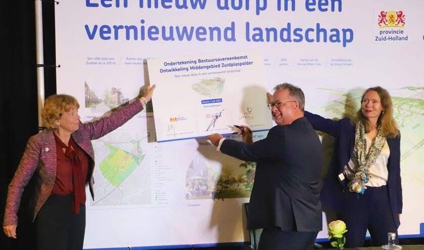 <p>Gedeputeerden Willy de Zoete (links) en Anne Koning zetten met burgemeester Han Weber hun handtekeningen.</p>