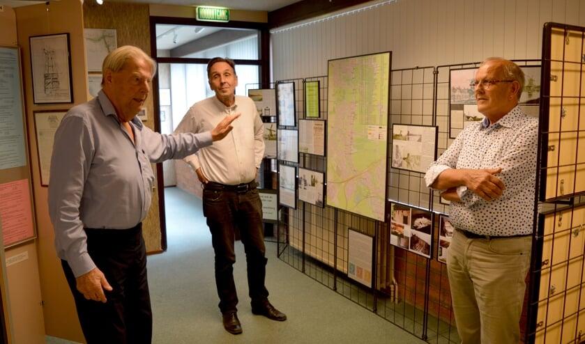 Dekker (links) geeft uitleg bij zijn Waddinxveense molententoonstelling; Van der Zalm en Ottevanger luisteren.
