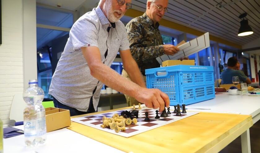 <p>Ben Balm inspecteert de schaakstukken die maandenlang ongebruikt opgeslagen lagen.&nbsp;</p>