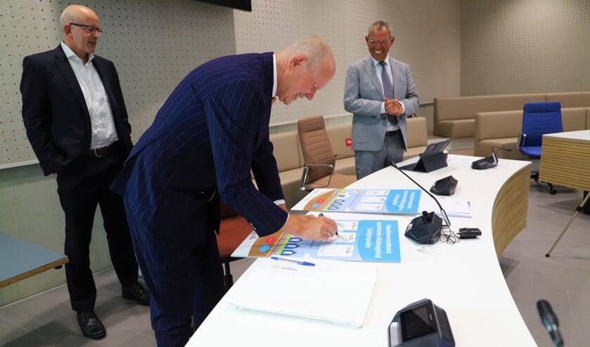 <p>Wethouders Jan Hordijk en Jan Verbeek zetten hun handtekeningen. (foto en tekst: Erik van Leeuwen)</p>