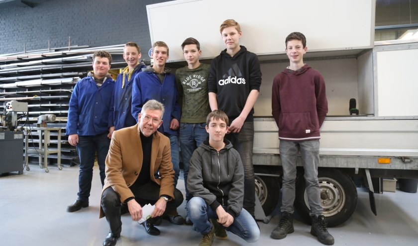 Van links naar rechts boven: BHC-leerlingen Bart, Ymre, Thomas, Lars, Stijn, Mark en rechtsonder Thijs biede IVN Best voorzitter Jan Ackermans (linksonder) hun zelfgemaakte aanhanger aan.   | Fotonummer: 36aa46