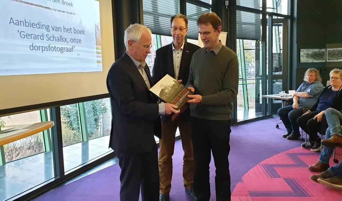 Gerard Schalkx (l.) met het eerste exemplaar van 'zijn' fotoboek, samen met wethouder Peter van de Wiel (r.) en Erfgoedvereniging Kék Liemt voorzitter Arnold van den Broek.
