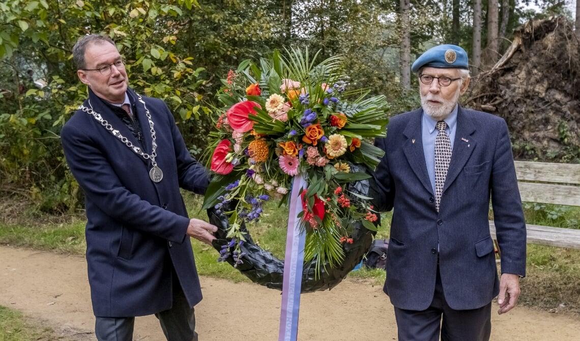 <p>Burgemeester Ronald van Meygaarden (l.) en Theo Raaijmakers leggen een krans bij het verzetsmonument.</p>