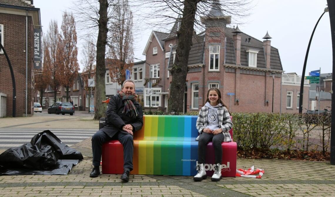 Wethouder Herman van Wanrooij en Tess Scheepers, zittend op het nieuwe regenboogbankje.