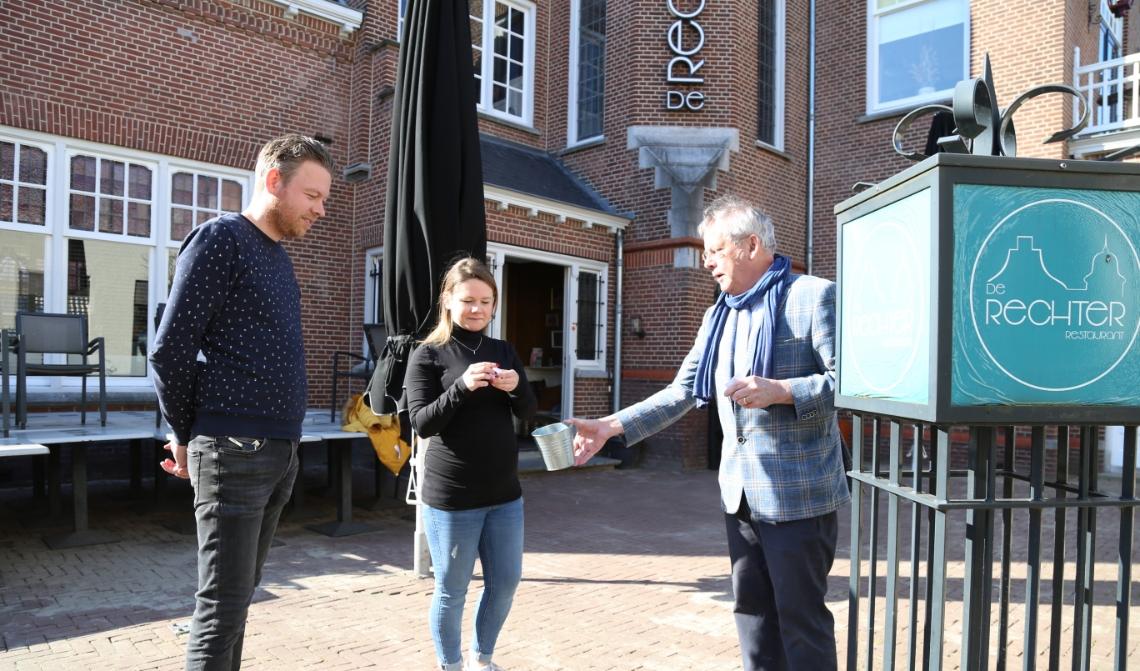 Corné Kuijpers (l.) kijkt toe hoe vaste gast Mirre de Folter een supermarkt trekt uit de 'grabbelton' die Voedselbank-voorzitter Arjen Witteveen vasthoudt.