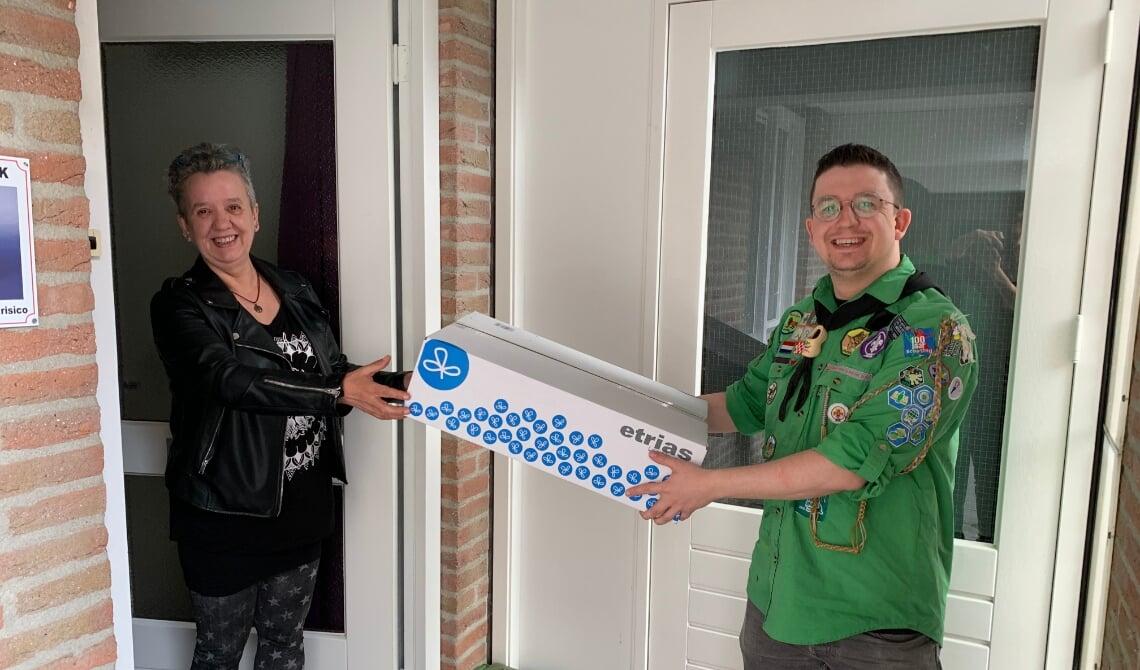 <p>Een moeder neemt de box in ontvangst, uit handen van de leiding. (Foto: Scouting Boxtel)</p>