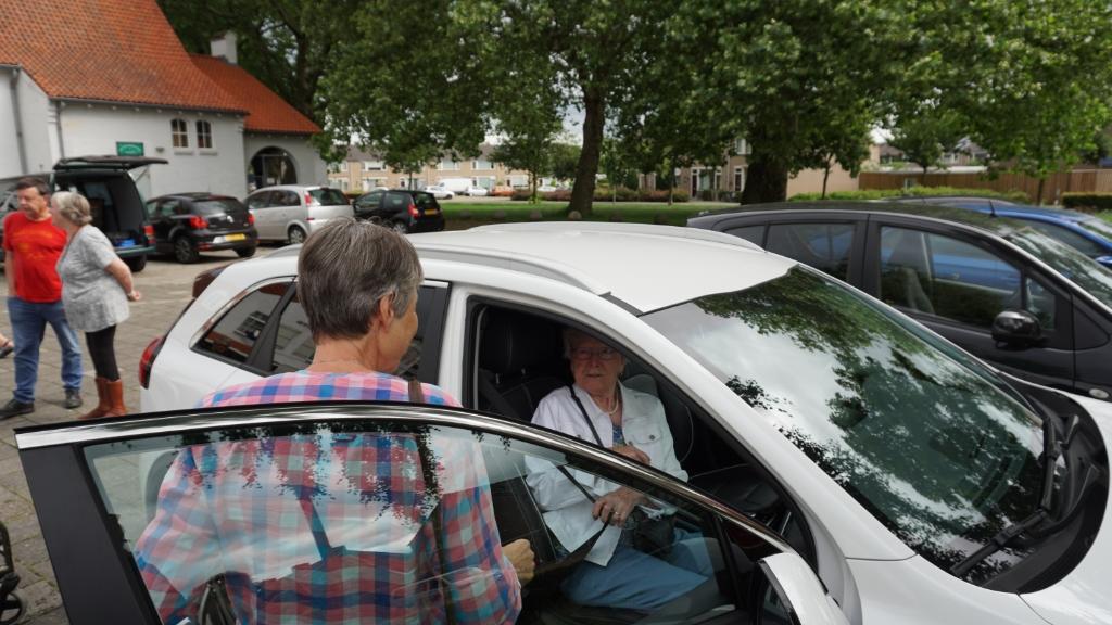 Mien van Weert wordt door mede-kartrekker van Seniorenvervoer Boxtel, Tineke Nuesink in de Kia e-Niro geholpen voor een proefrit. Foto: Sander van Kasteren © MooiBoxtel