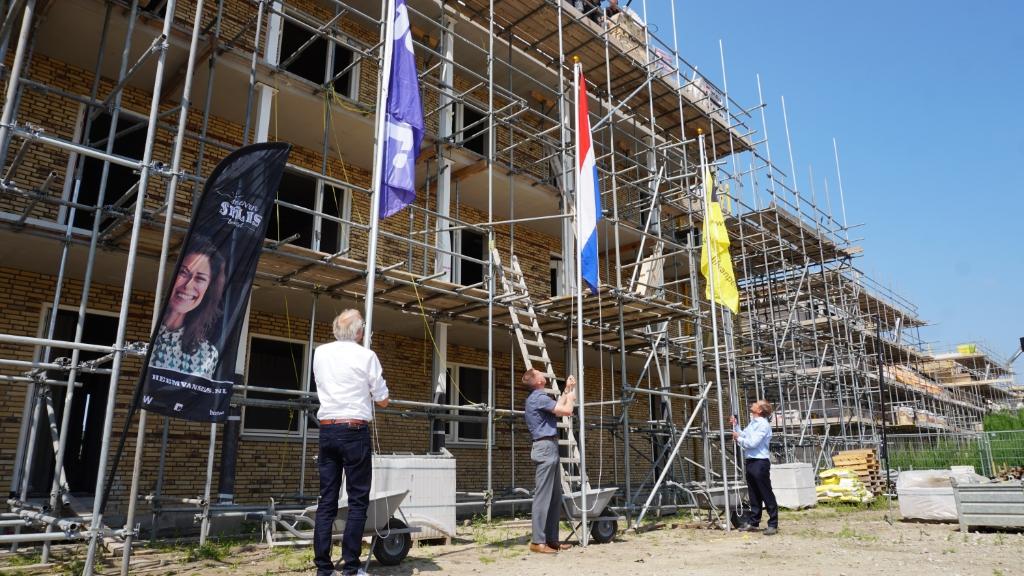 Wethouder Wim van der Zanden (m.) hijst samen met directeur-bestuurder Rob Dekker van Woonstichting JOOST (l.) en Jan van Peer van Bouwbedrijf Van Peer de vlag bij het nieuwe appartementencomplex. Foto: Sander van Kasteren © MooiBoxtel