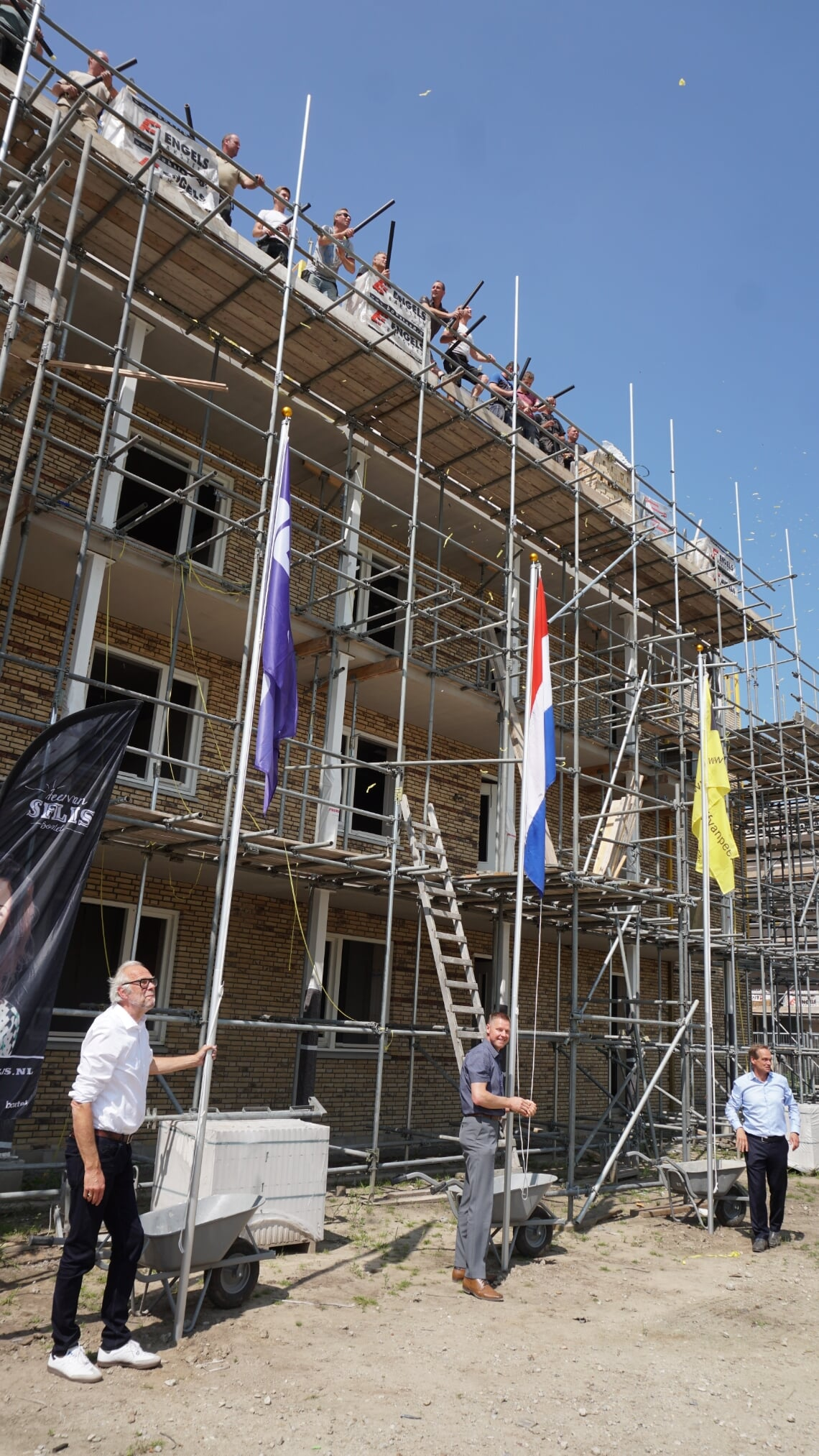 Wethouder Wim van der Zanden (m.) hijst samen met directeur-bestuurder Rob Dekker van Woonstichting JOOST (l.) en Jan van Peer van Bouwbedrijf Van Peer de vlag bij het nieuwe appartementencomplex.