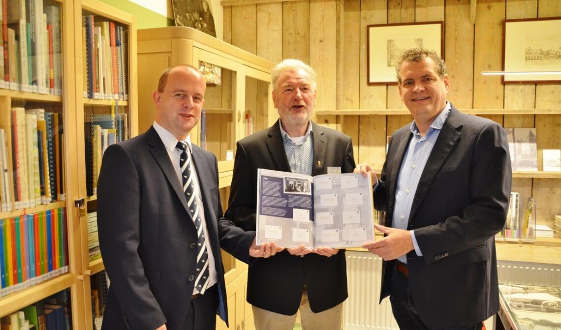 <p>Jumbo-filiaalleider Oskar Martens (l.) en Heemkunde Boxtel voorzitter Henk van Beers (m.) overhandigen het eerste exemplaar van het spaarboek aan cultuurwethouder Hans Heesen. (Foto: Jan van der Steen)</p>