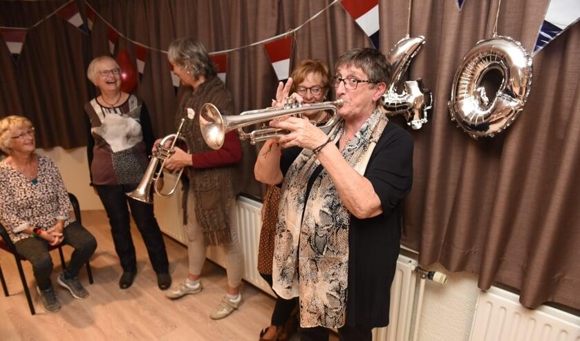 Voorzitter Joke de Witte probeert de trompet uit.
