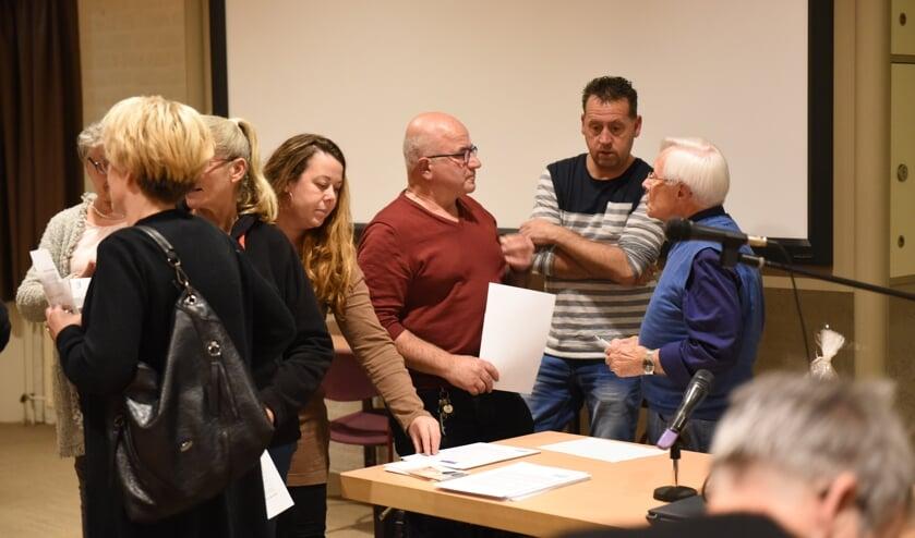 Bezoekers praten na met spreker Jan Kamerling (rechts)