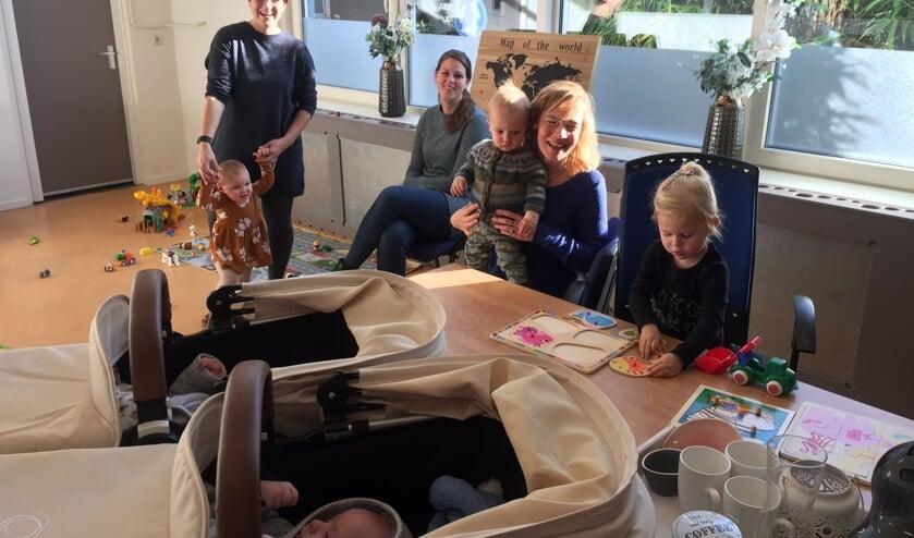 Dorien Lomeijer (midden achter) ziet hoe haar dochter Evi speelt aan de tafel waarop de maxi-cosi's met haar broertje Joey en zusje Lisa – een tweeling – staan. Links Sharita van der Meulen met dochter Eora en rechts Marieke Heinsbroek met zoontje Kees op schoot.