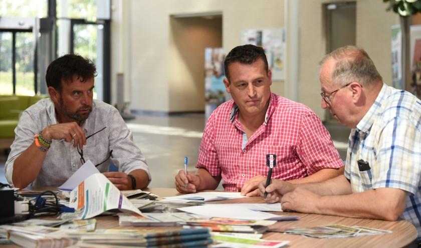 VVD-raadsleden Anco Fase, Arjan Deurloo en Ad Hommel bespreken tijdens een schorsing hun standpunten over de moties. De liberalen stemmen als coalitiepartij voor belastingverhoging, maar met tegenzin.