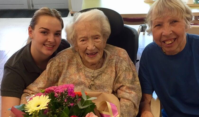 De jarige mevrouw Van Oosterhout is in De Nieuwe Haven in de bloemen gezet. Links stagiaire Amber Kok, rechts bewoonster Marianne Bakker.