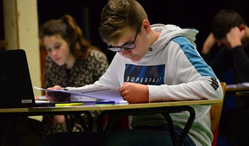 <p>Niels Krijger werkt aan zijn eindexamen Nederlands in de gymzaal van het Calvijn College in Tholen.</p>