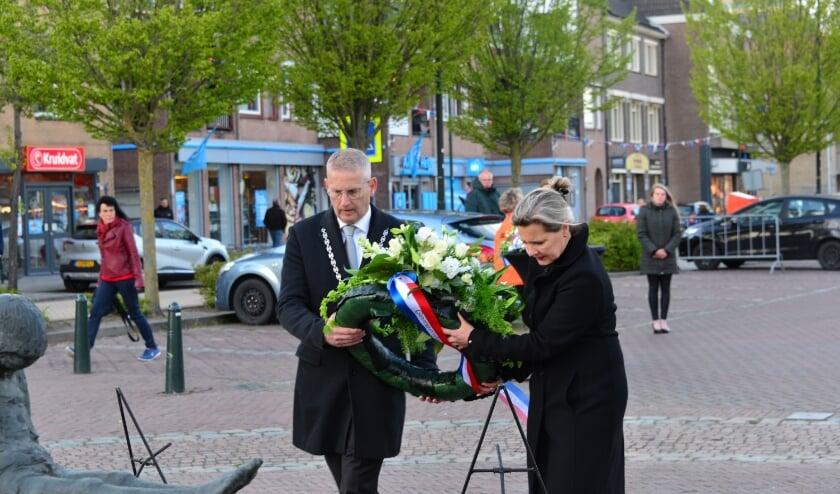 Burgemeester en mevrouw Van den Belt leggen een krans bij het monument op het Raadhuisplein.