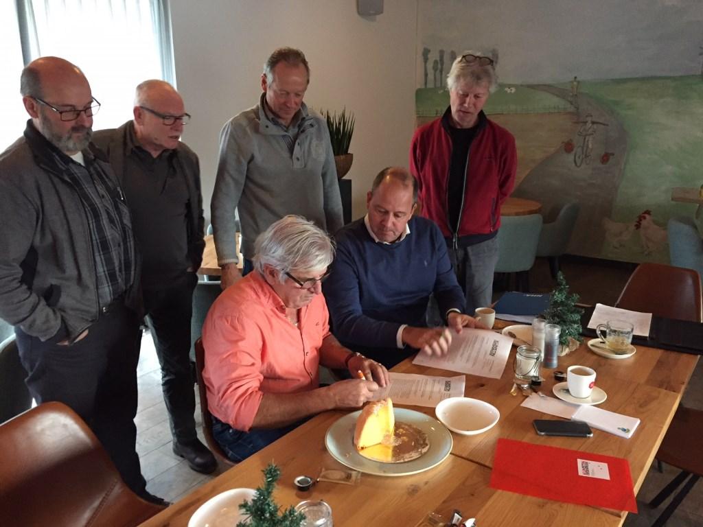 Joost van Dijk (voorzitter Kunststichting) en Piet Klaasen (voorzitter Oud-Rijsingen) tekenen de overeenkomst, de andere bestuursleden kijken kritisch toe.  © MooiRooi