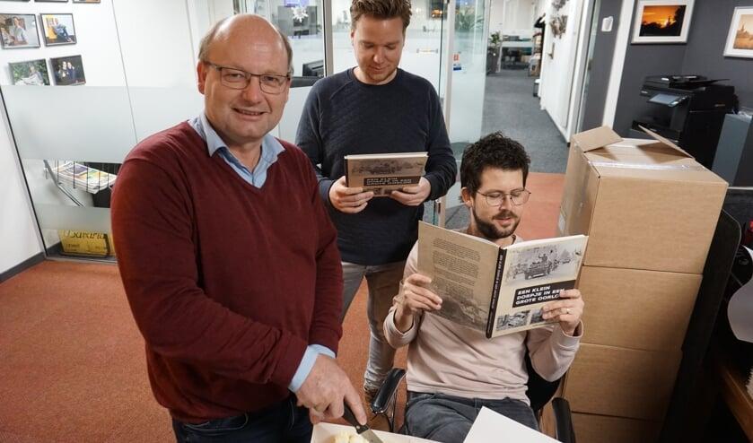 Schrijver Hans snijdt de taart aan. Naast hem ontwerper Ruud van der Pol en hoofdredacteur van DeMooiRooiKrant, Jeroen van de Sande.   | Fotonummer: e5a690