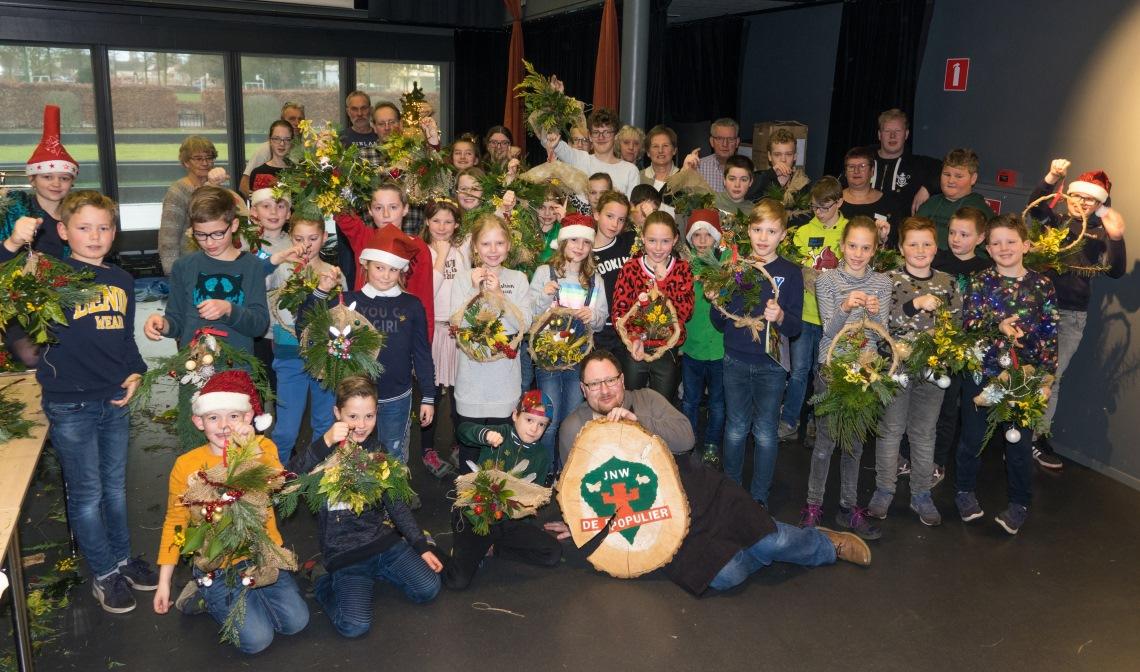 De jeugdnatuurwachters met hun eigengemaakte kerststuk samen met de leiding en wethouder Van der Pas.