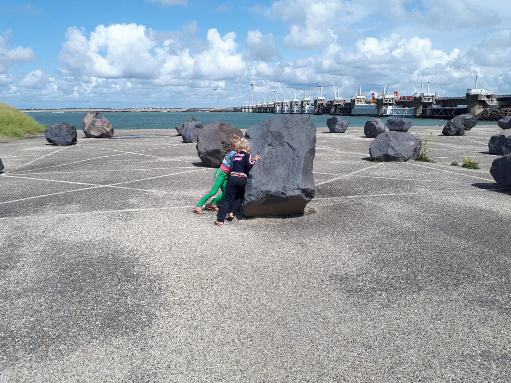 Mila en Tess proberen een steen te verleggen bij de Oosterscheldekering. Foto: Mieke Vervoort   © MooiRooi