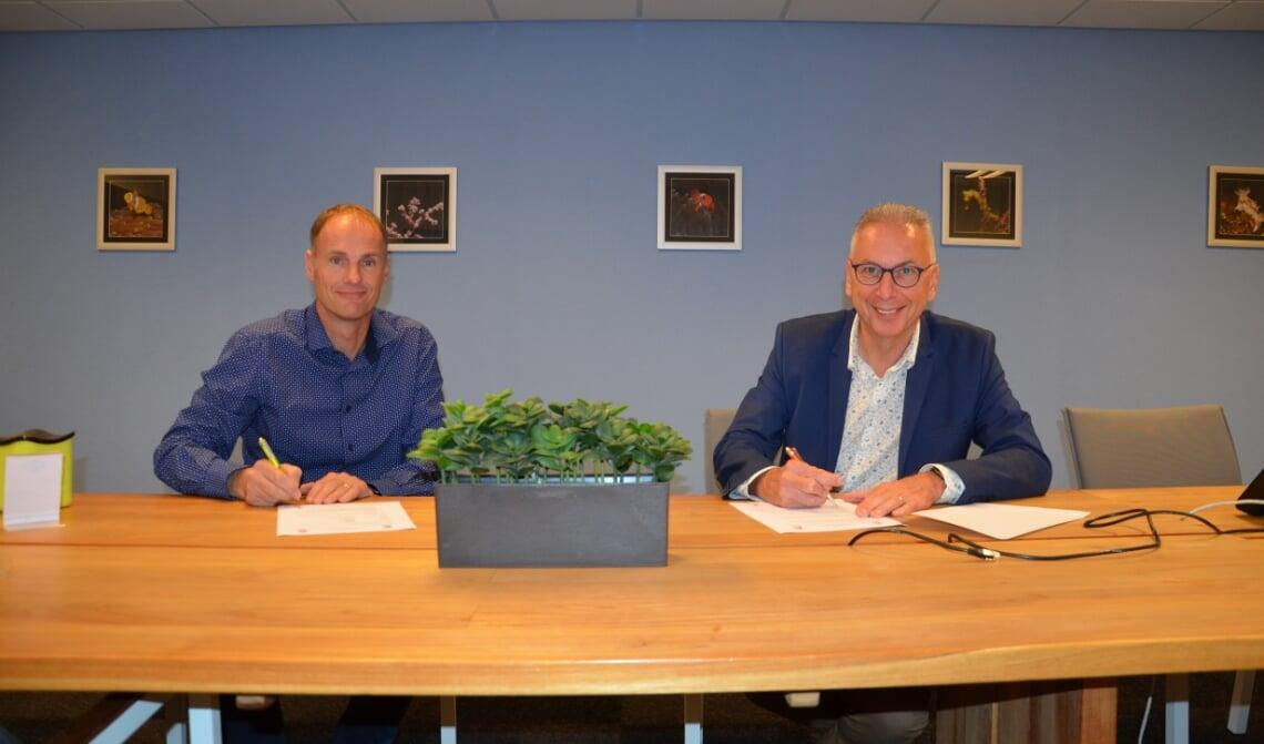 <p>Mark de Wit en Ad van Acht (r) tekenen een nieuw contract.</p>