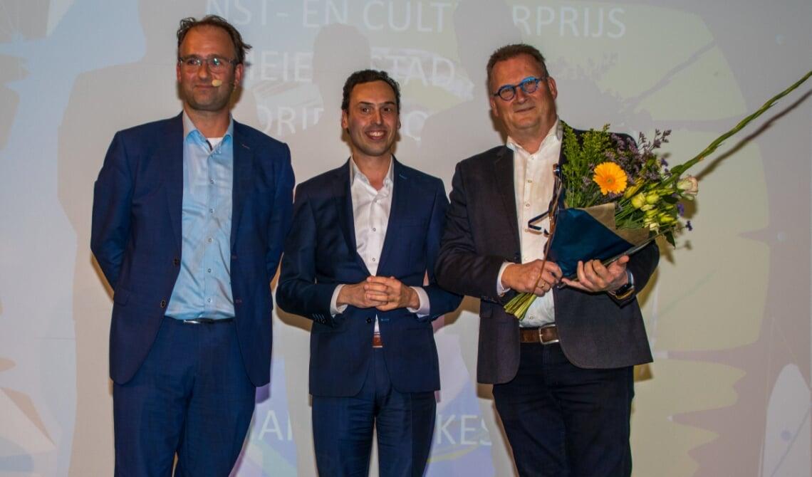 <p>Marc van Kessel (r) kreeg de prijs uit handen van gedeputeerde van de Provincie dhr. Smeulders. Links is wethouder Menno Roozendaal. Hij praatte de avond aan elkaar met een presentator.&nbsp;</p>