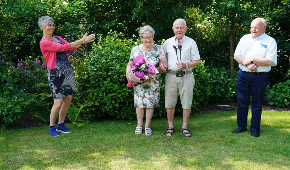 <p>Corrie en Piet met hun cadeaus in de eigen achtertuin. Links Ria Hilhorst, rechts Martien Bekkers.</p>