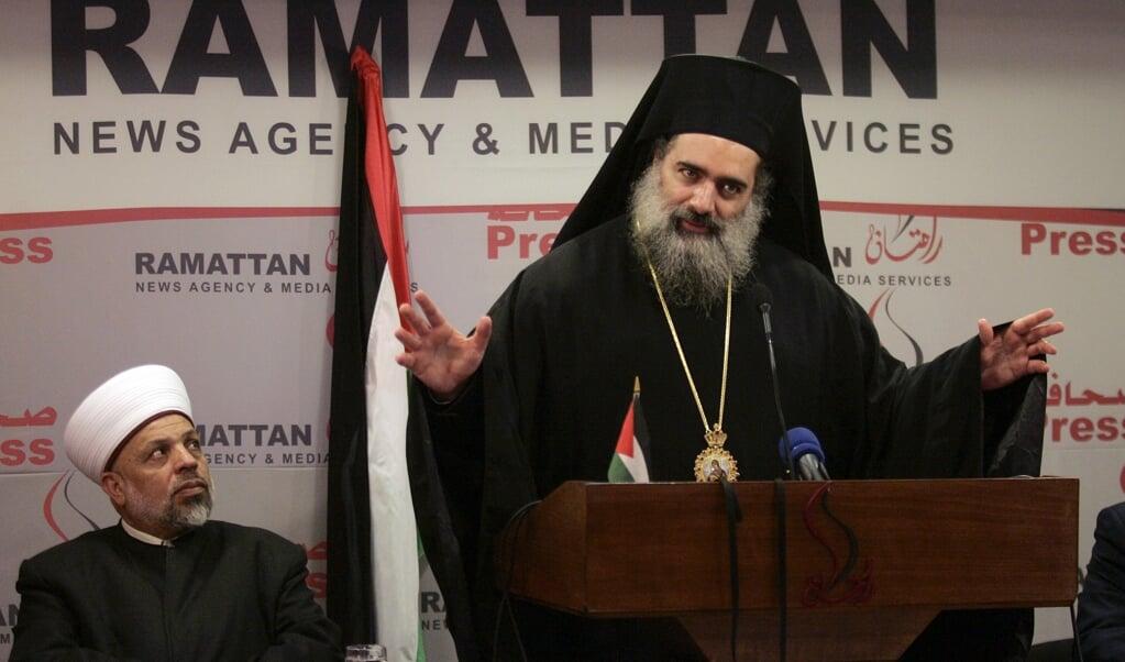 Aartsbisschop Atallah Hanna (staand) tijdens een persconferentie in 2008.  (beeld afp / Abbas Momani)